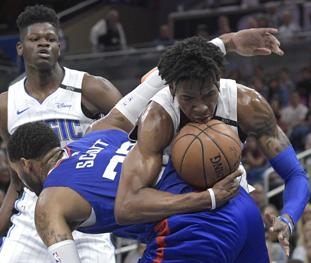 Orlando's Wesley Iwundu, right, is fouled by Mike Scott of the Clippers after grabbing a rebound in Friday's game at Orlando, Fla.