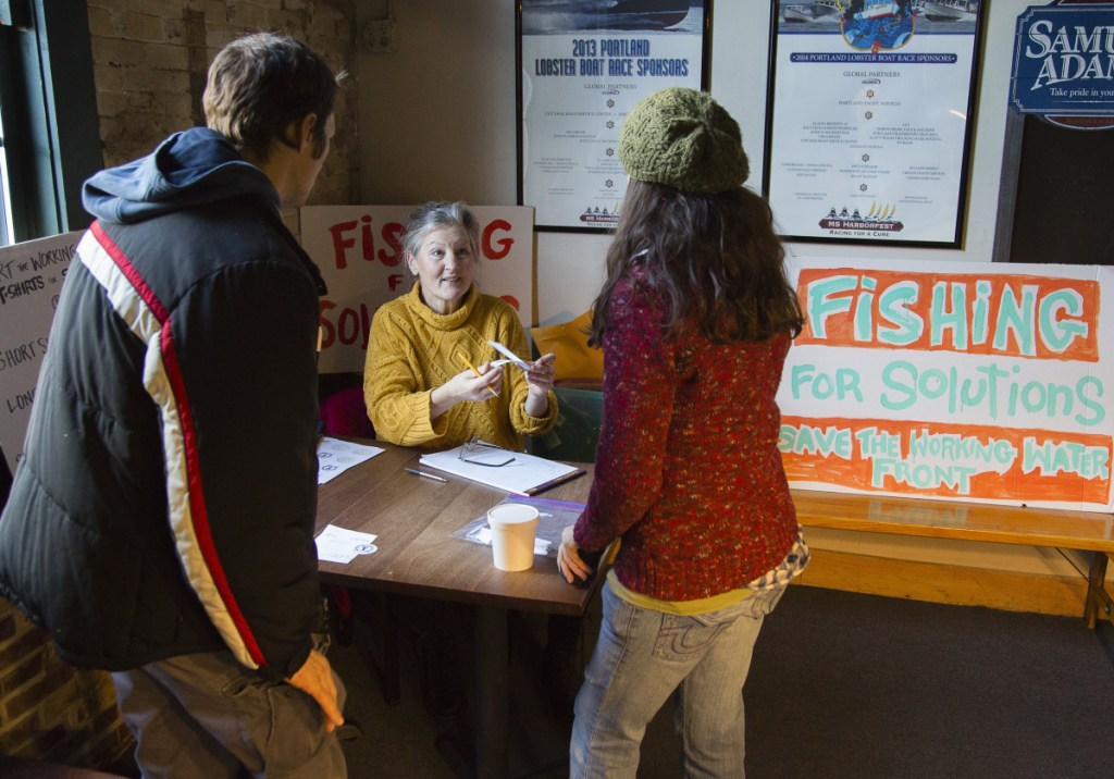 Volunteer Joanne Arnold of Falmouth offers raffle tickets to Stanislav Yurkuvich and Alex Fagan of Portland, during a petition drive and fundraiser at Andy's Old Port Pub on Sunday.
