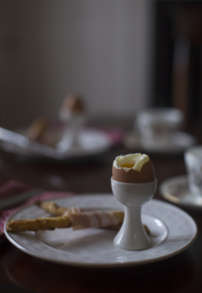 Soft-boiled eggs with prosciutto and cheese soldiers served with tea. The soldiers, for dipping in the eggs, are made from pie dough scraps, a great way to make use of the trimmings from holiday pies.