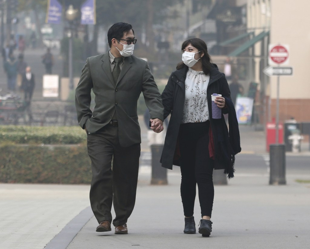 Tashi Nacario and Samantha Salas wear masks to deal with the smoke from the Camp Fire that shrouds the state Capitol on Thursday in Sacramento, California. Smoke from the blaze that burned through the Butte County city of Paradise is creating a health hazard that experts say could lead to an increase in serious health problems, especially for children and the elderly.