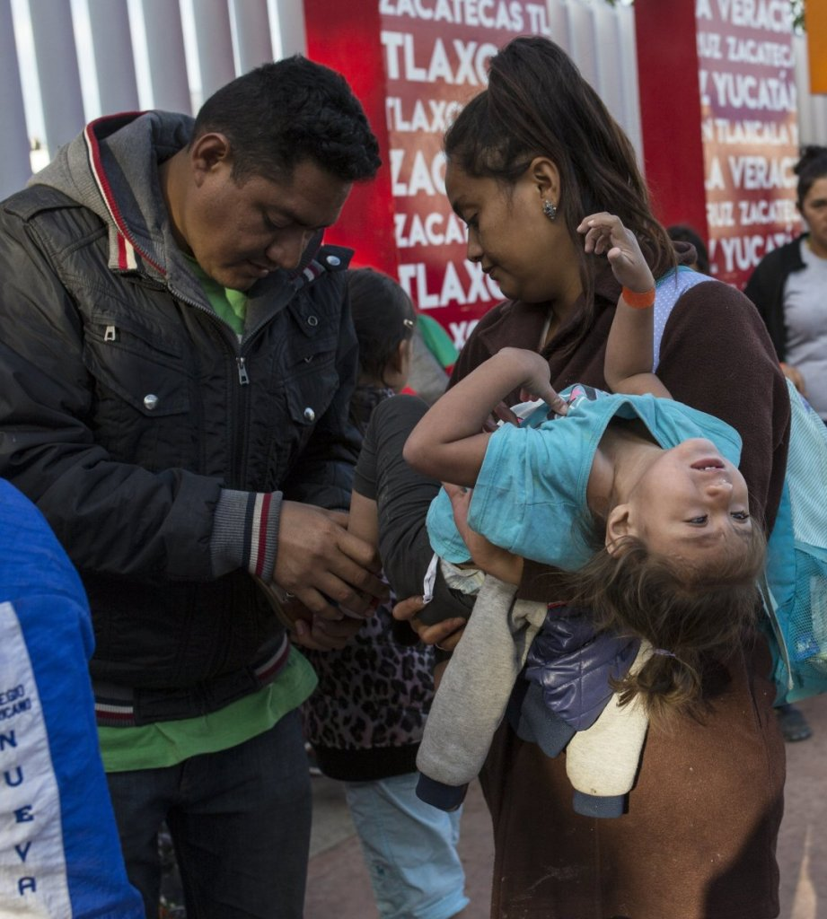 A Central American family, left, waits in line to begin the asylum process in Tijuana, Mexico in November.