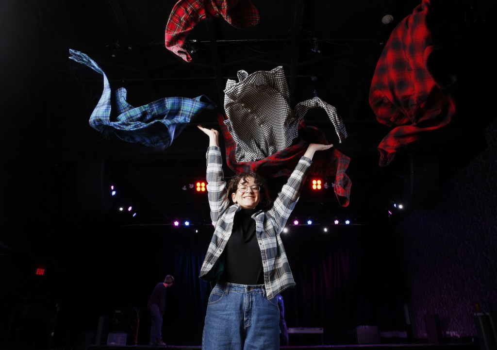 Caroline Kouba, a first-year Maine College of Art student, models a flannel shirt last week at Port City Music Hall. The fabric sometimes identified with lumberjacks is also being embraced by millennials, leading to a spike in sales.