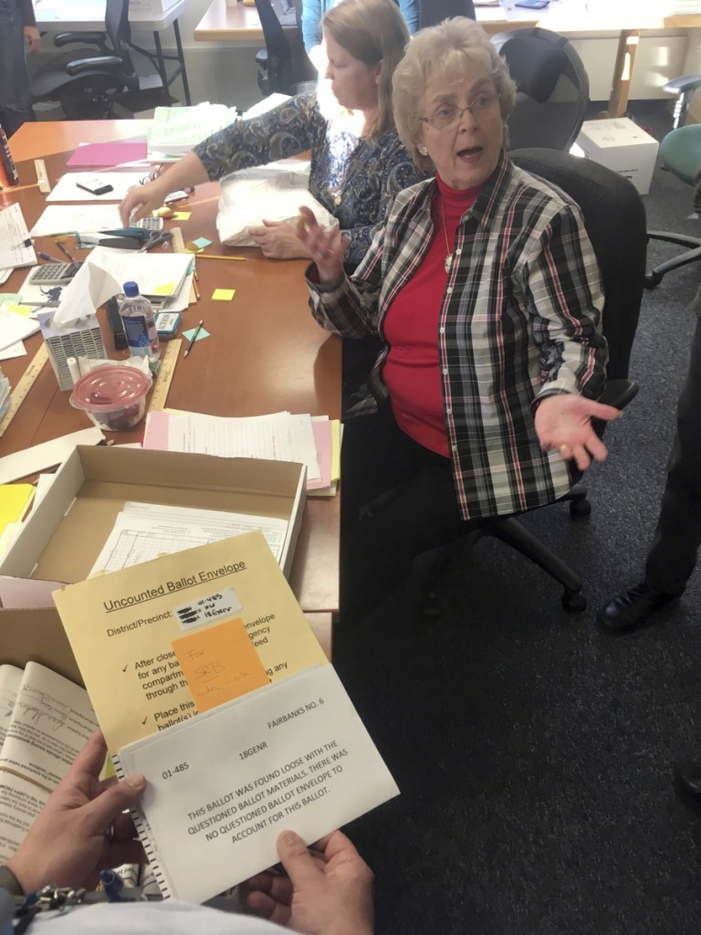 A State Review Board ballot examiner reacts when a loose ballot from a tied state House race is found without an envelope in Alaska.