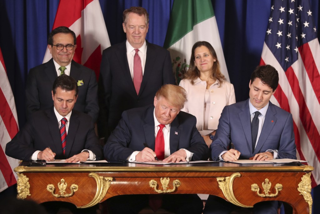 President Trump sits between Canada's Prime Minister Justin Trudeau, right, and Mexico's President Enrique Pena Nieto as they sign the United States-Mexico-Canada Agreement, which that is replacing the NAFTA trade deal, during a ceremony Friday at a hotel before the start of the G20 summit in Buenos Aires, Argentina. The USMCA, as Trump refers to it, still nneds approvald by lawmakers in all three countries.