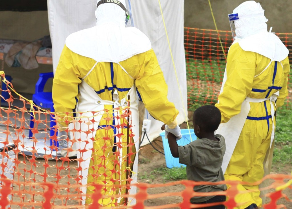 Health workers walk with a boy suspected of having the Ebola virus at an Ebola treatment center in Beni, Eastern Congo, in September.