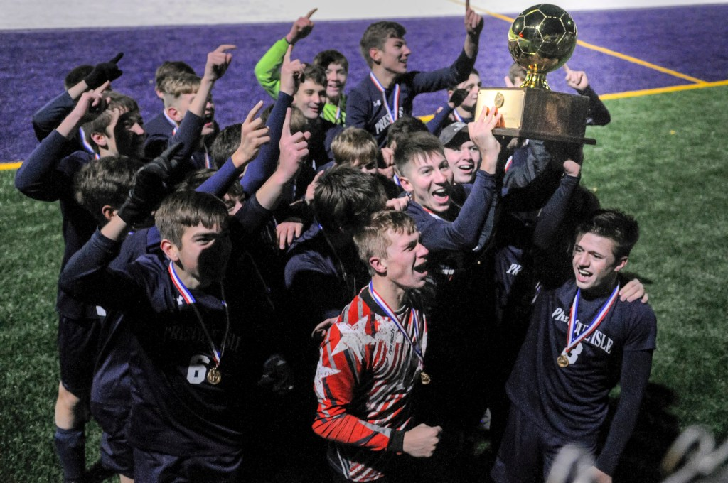 Presque Isle celebrate with the gold ball trophy after beating Freeport 3-2 in the Class B boys soccer state championship on Saturday in Hampden.
