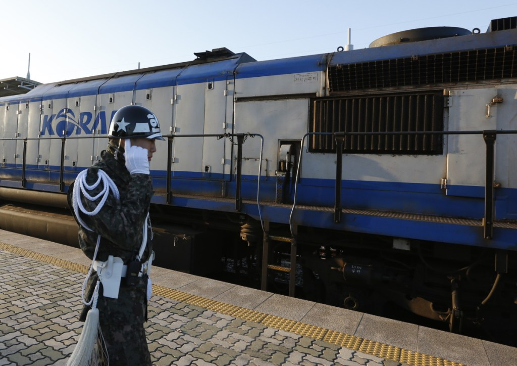 A South Korean soldier stands next to the train about to travel across the border into North Korea at the Dorasan Station in Paju, South Korea, Friday. The train pulled six cars filled with dozens of South Korean expert and officials who will undertake an 18-day, 750-mile survey of railway tracks in the North.