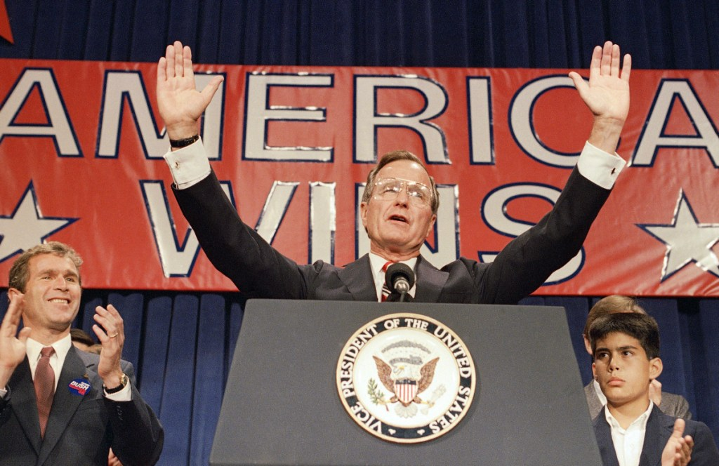 """President-elect George H. W. Bush speaks at his victory rally with grandson, George P. Bush, right, and son George W. Bush, left, in Houston on Nov. 9, 1988. In one of his presidency's most memorable moments, Bush reneged on his """"No new taxes"""" pledge, angering conservative Republicans and laying the groundwork for the GOP of today."""