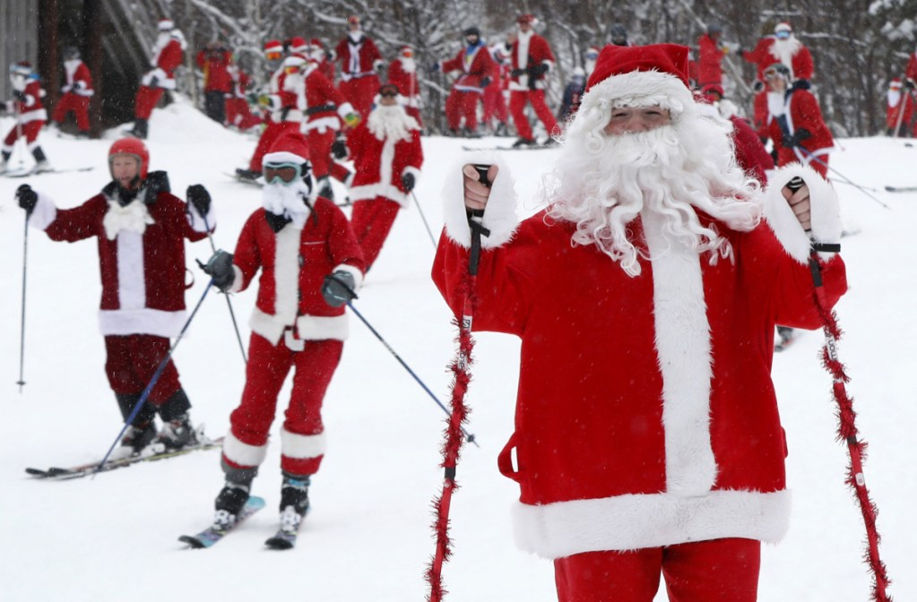 Skiers and snowboarders dressed as Santa Claus head downhill during the annual Santa Sunday event in Newry. The red-suited lookalikes aim to put a smile on people's faces while raising money for charity. Associated Press/Robert F. Bukaty