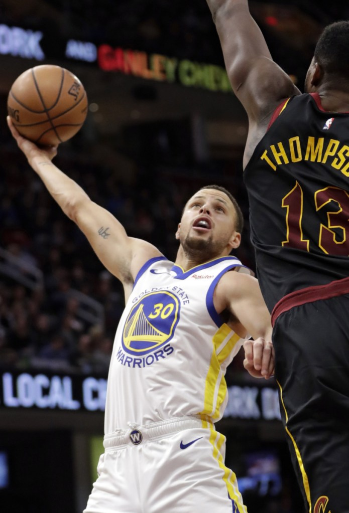 Golden State's Stephen Curry, left, drives against Cleveland's Tristan Thompson during Wednesday's game in Cleveland. The Warriors won 129-105.