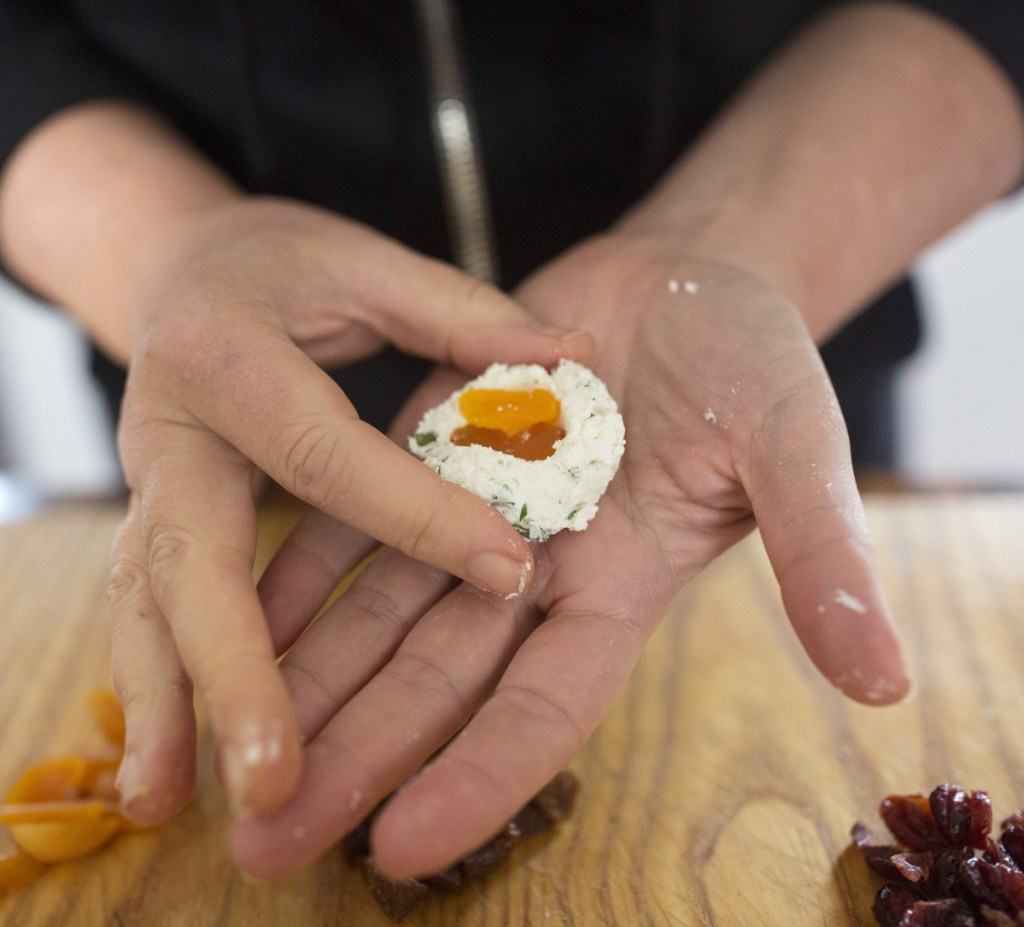 Christine Burns Rudalevige stuffs a ball of goat cheese with dried apricots before coating it with pistachios.