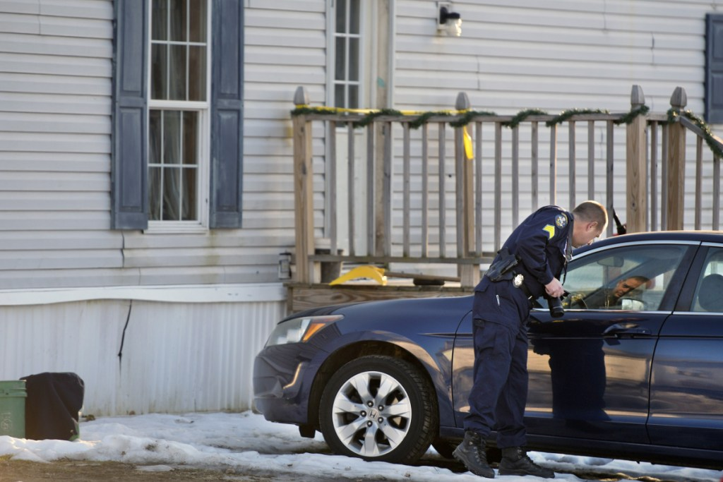 Maine State Police Detective Sgt. Jason Richards examines vehicles outside a residence on the Post Road in Richmond on Saturday.