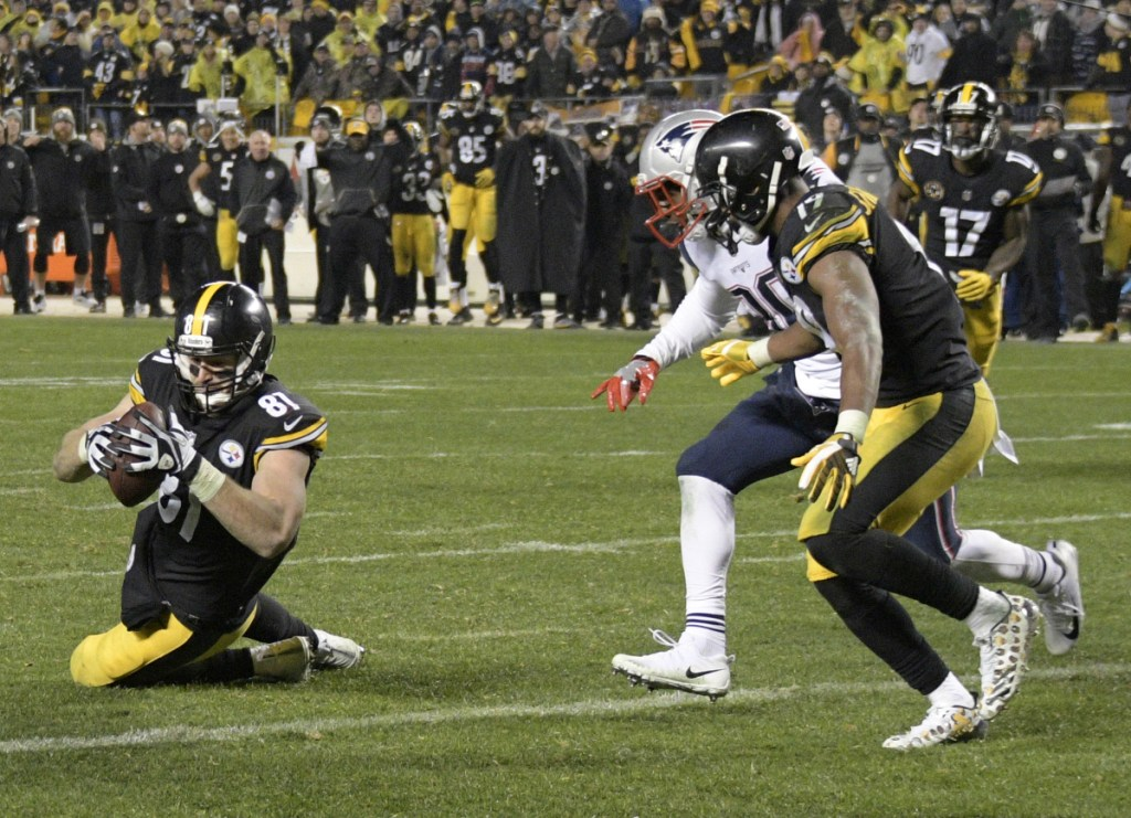 The catch wasn't a catch for Pittsburgh's tight end Jesse James, left, last December against the Patriots. The apparent touchdown was reversed in the final minute, and New England held on for a 27-24 win, securing the top seed in the AFC.