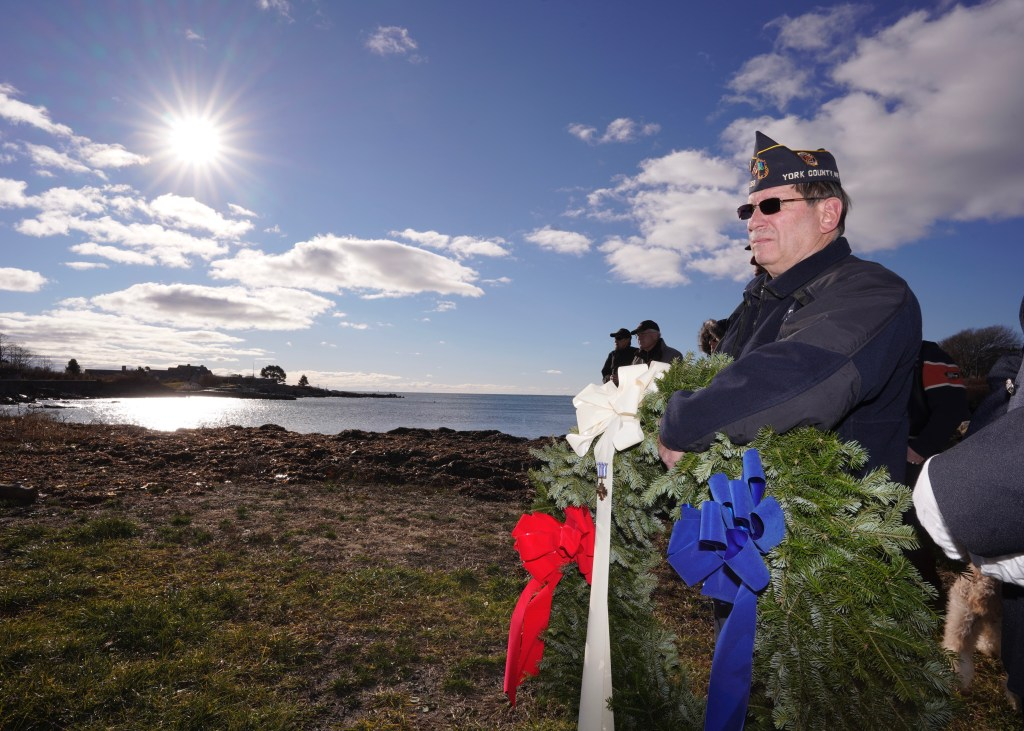 Tom Willey of the American Legion Post 159 in Kennebunkport holds a wreath during a ceremony honoring George H.W. Bush across from Walker's Point in Kennebunkport on Tuesday.