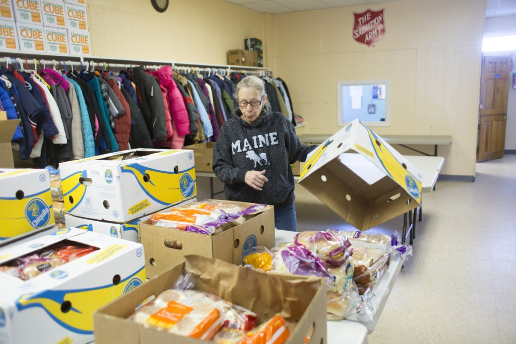 Volunteer Deborah Berry sorts food donations Thursday at the Salvation Army in Sanford. A safe containing $1,700 in donations was burglarized over Christmas, but the community quickly covered the loss. And then some.