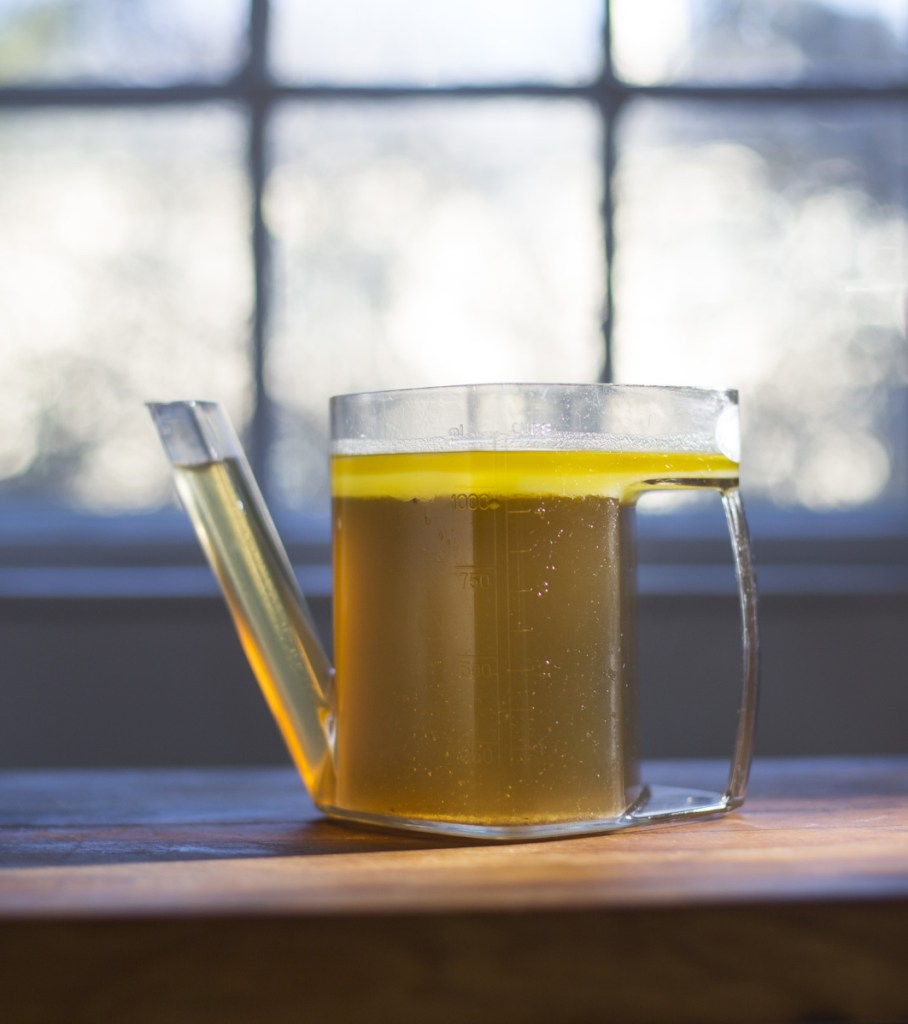 Yellow fat sits atop stock in a fat separator. Top: Chicken and egg drop soup, made with the stock.