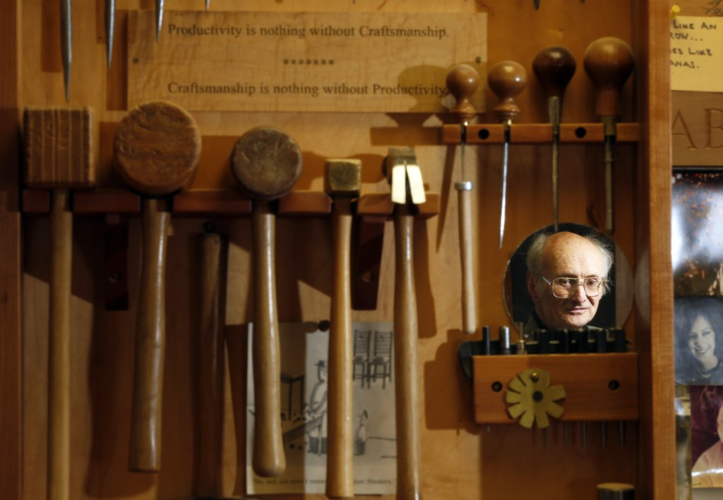 "Master woodworker Christian Becksvoort is reflected in a mirror on the tool chest in his New Gloucester shop, where a sign reads ""Productivity is nothing without Craftsmanship ... Craftsmanship is nothing without Productivity."""