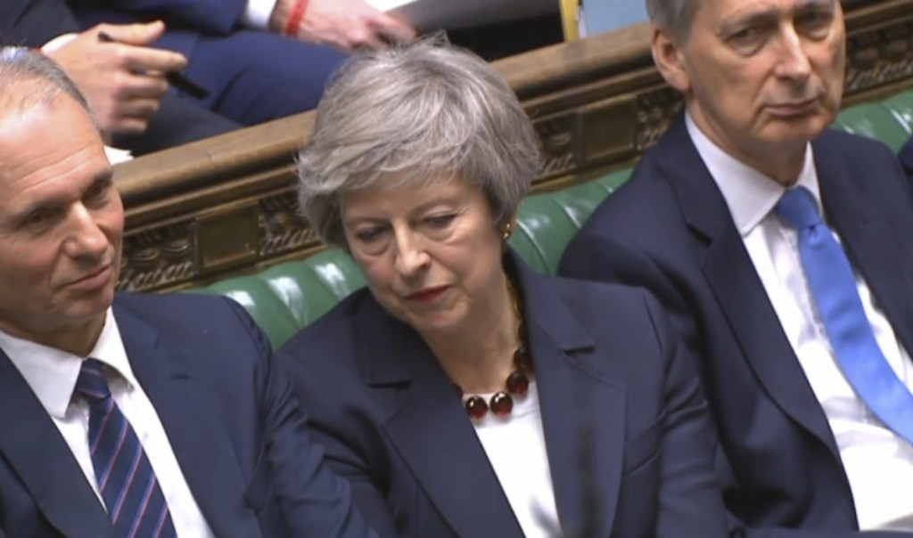 In this grab taken from video, Britain's Prime Minister Theresa May, centre, listens during Prime Minister's Questions in the House of Commons, London, Wednesday, Jan. 9, 2019.  The British government brought its little-loved Brexit deal back to Parliament on Wednesday, a month after postponing a vote on the agreement to stave off near-certain defeat. (House of Commons/PA via AP)