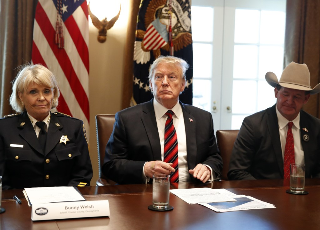 """President Trump, with Carolyn """"Bunny"""" Welsh, sheriff of Chester County, Pa., left, and A.J. Louderback, sheriff of Jackson County, Texas, attends a roundtable discussion on border security with local leaders Friday."""