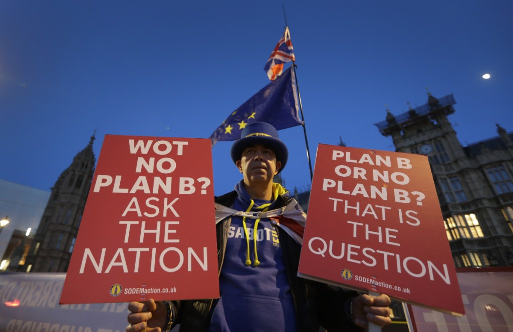 A pro-European demonstrator holds banners near Parliament in London on Thursday. British Prime Minister Theresa May is reaching out to opposition parties and other lawmakers in a battle to put Brexit back on track after surviving a no-confidence vote. (AP Photo/Kirsty Wigglesworth)
