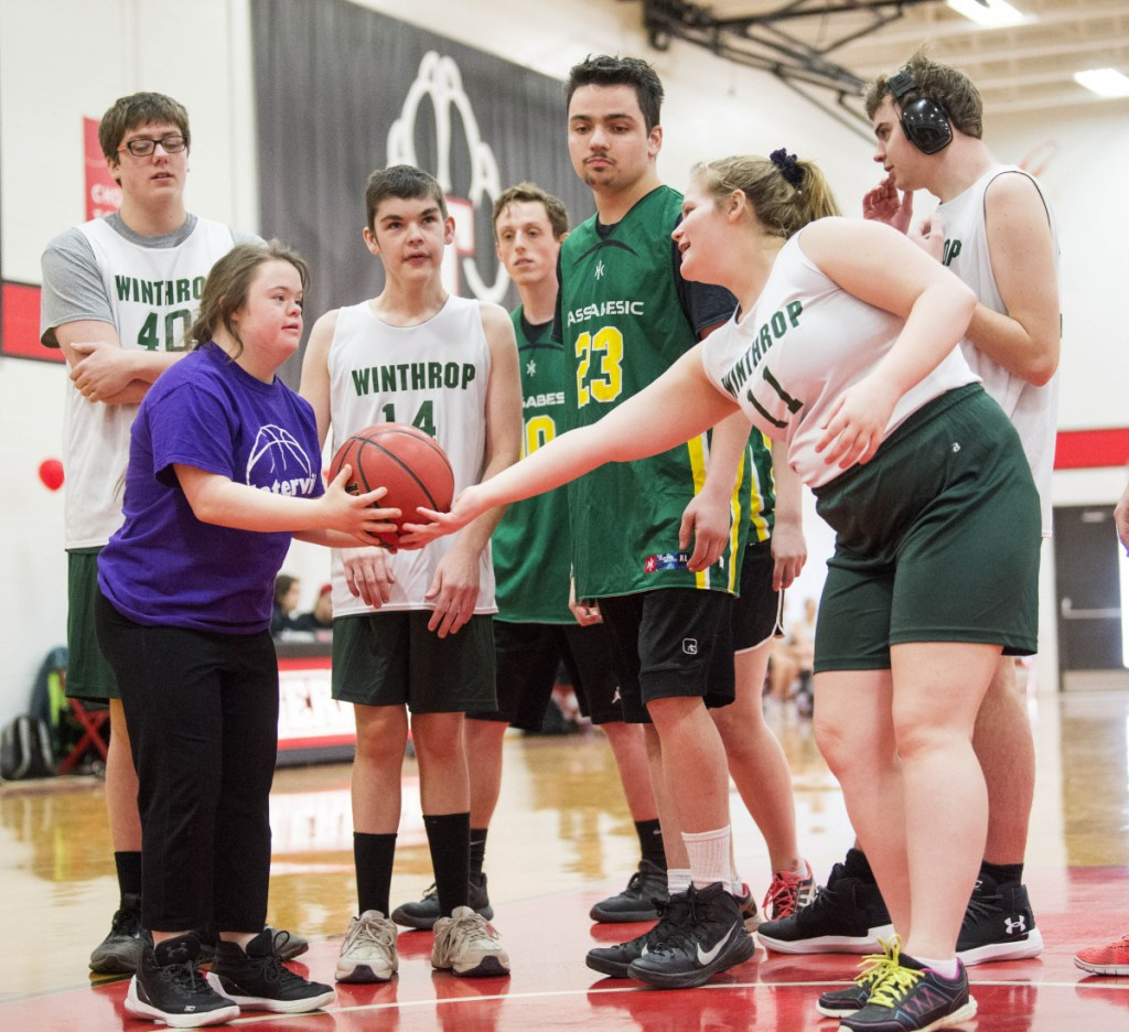 Samantha Neumann of Winthrop hands the ball to an opponent from Waterville for another shot at the Unified basketball tournament Saturday.