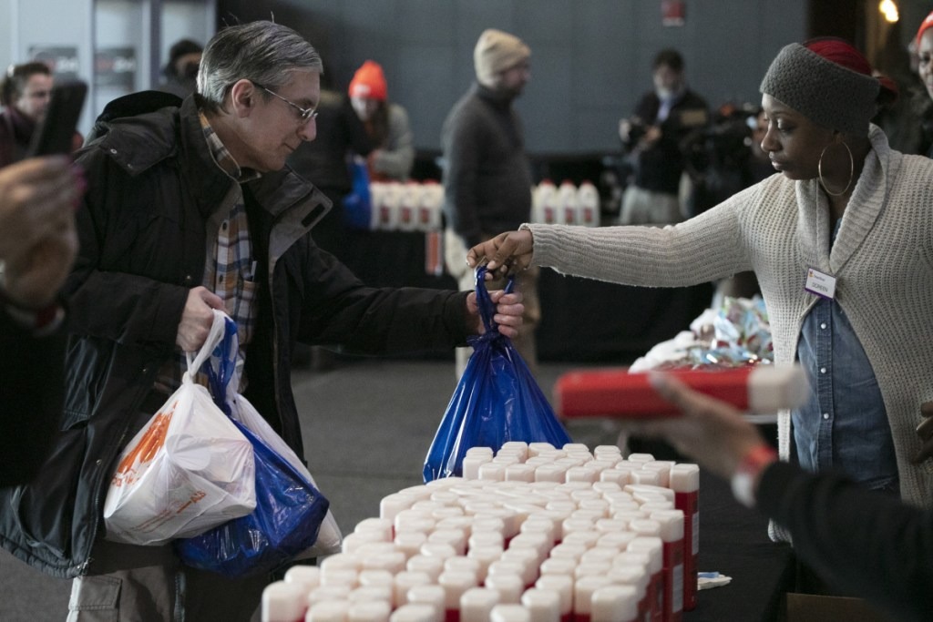 A government worker, left, gets groceries at a food bank for government workers affected by the shutdown, on Tuesday, the 32nd day of the shutdown, in the Brooklyn borough of New York.