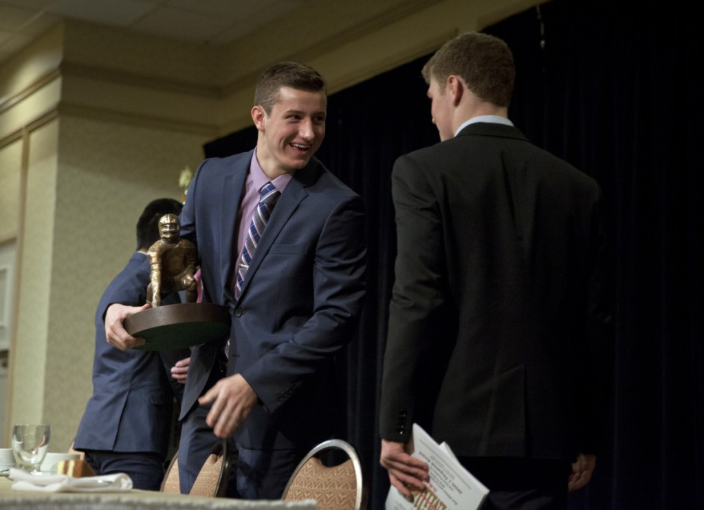Tyler Bridge, left, of Wells is congratulated by Zack Elowitch of Portland after receiving the Fitzpatrick Trophy at the Holiday Inn by the Bay in Portland on Sunday. Elowitch and Anthony Bracamonte of Thornton Academy were the other finalists.