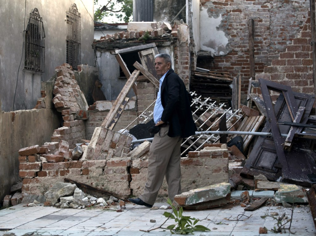 A man walks in a home that was destroyed by a tornado in Havana, Cuba, Monday, Jan. 28, 2019. A tornado and pounding rains smashed into the eastern part of Cuba's capital overnight, toppling trees, bending power poles and flinging shards of metal roofing through the air as the storm cut a path of destruction across eastern Havana. (AP Photo/Ramon Espinosa)