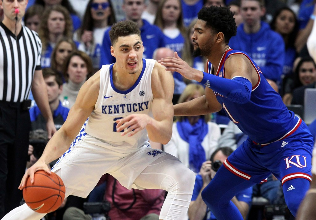 Kentucky's Reid Travis (22) drives on Kansas' Dedric Lawson during the second half of the Wildcats' 71-63 win Saturday in Lexington, Ky.