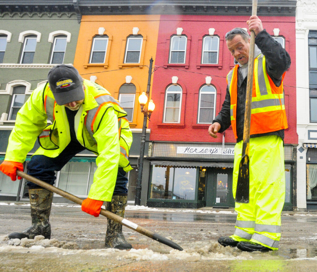 Augusta Public Works employee Rick Allen, left, shovels up pieces of ice that Lee Edwards chopped off a Water Street storm drain on Thursday in downtown Augusta. The warm, rainy weather had state and local crews out clearing drains to avoid flooding.