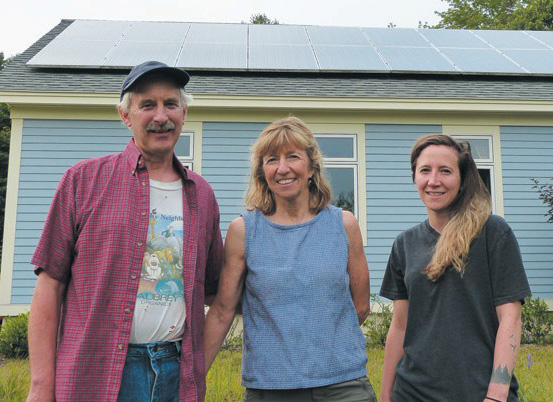 From left, Jake Plante, Marcia Harrington and Alexandra Plante stand in front of the solar panels mounted on the garage at their Rossmore Road home in Brunswick. The solar panels were assessed by the town and taxed as real property, a decision Plante, Harrington and six other property owners with solar panels are seeking to have overturned.