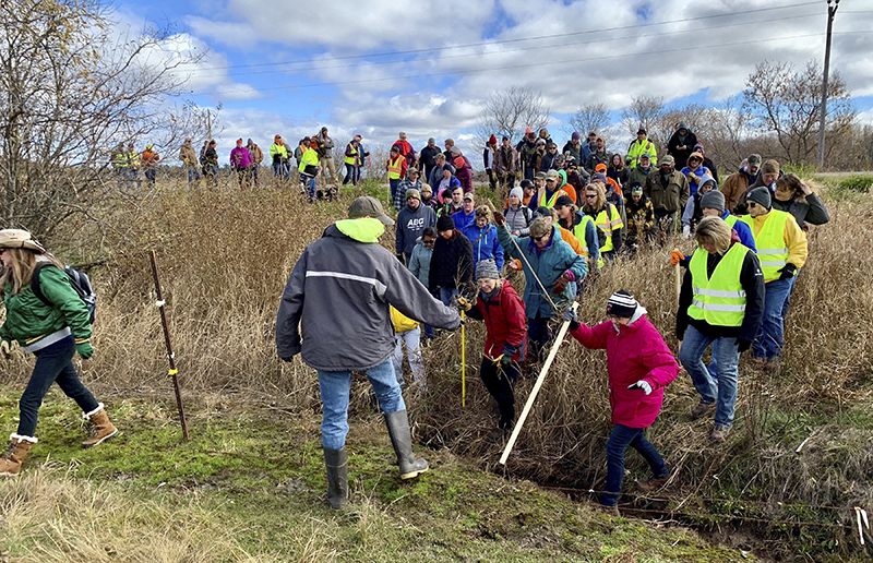 Volunteers cross a creek and barbed wire near Barron, Wis. on Oct. 23, on their way to a ground search for 13-year-old Jayme Closs who was discovered missing Oct. 15 after her parents were found fatally shot at their home.