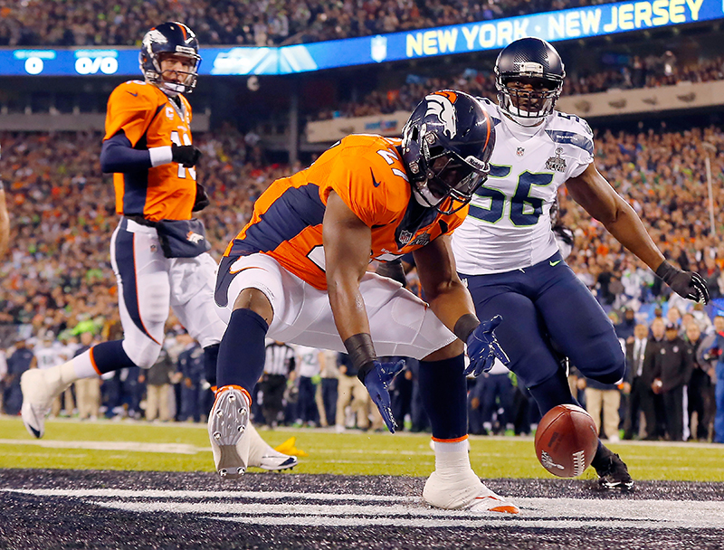 Denver Broncos Knowshon Moreno reaches for a loose ball in the end zone after the snap sailed past quarterback Peyton Manning, left, on the first play from scrimmage in Super Bowl XLVIII, Feb. 2, 2014. The Seahawks never looked back, winning 43-8 for their first Super Bowl championship.
