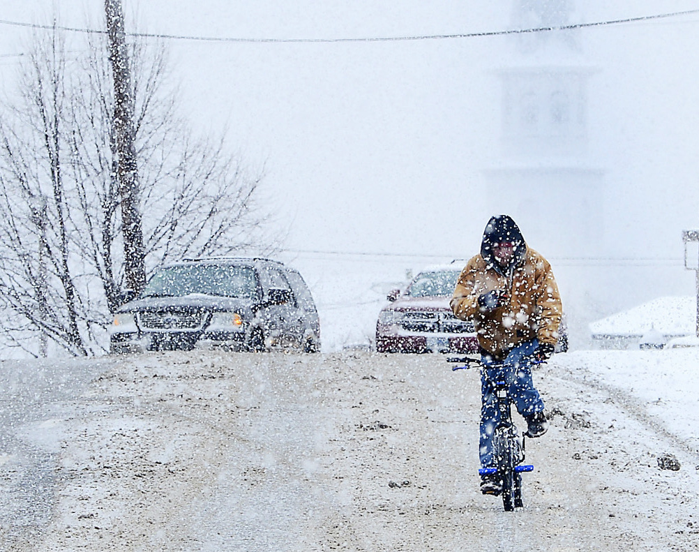 A cyclist rides through snow on U.S. 40 during a winter storm Friday in Hagerstown, Md.