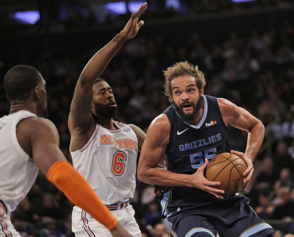 Memphis's Joakim Noah, right, drives to the basket during the first half of the Grizzlies' 96-84 win over the New York Knicks on Sunday in New York.