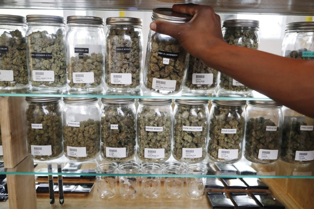 A clerk reaches for a container of marijuana buds for a customer at Utopia Gardens, a medical marijuana dispensary in Detroit.