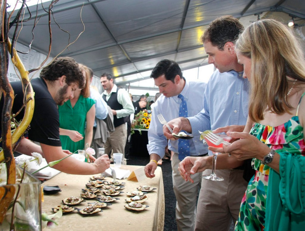 From right, Erin and Kevin Morneault of Falmouth and Mark Simmons of Concord, N.H., watch while Hugo's chef Andrew Taylor serves Gedalis Farm Goat Taquitos at Taste of the Nation on June 27, 2010.