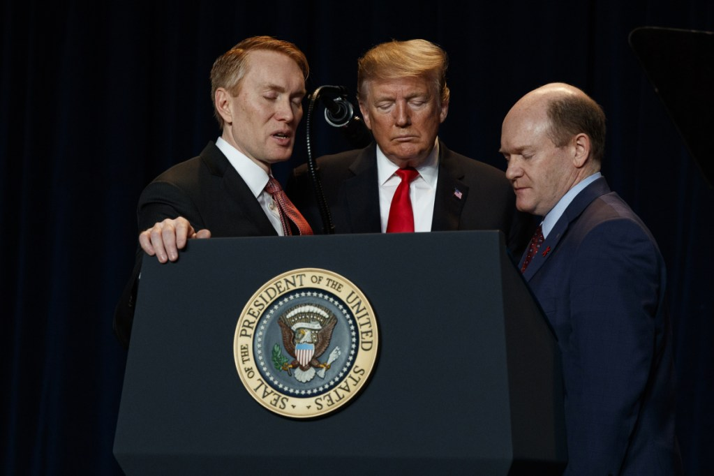 Rep. James Lankford, R-Okla., left, President Trump, center, and Sen. Chris Coons, D-Del., pray during the National Prayer Breakfast on Thursday in Washington. (AP Photo/ Evan Vucci)