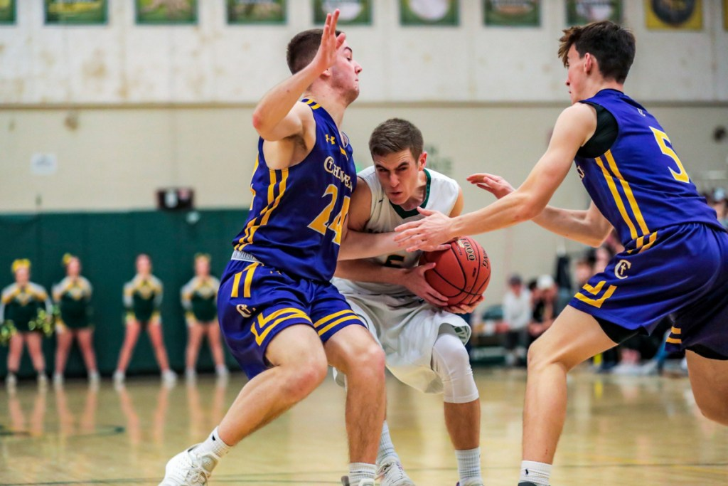 Garrett Record of Oxford Hills tries to squeeze between Patrick Foster, left, and Owen Burke of Cheverus during their Class AA North basketball quarterfinal Wednesday night. Oxford Hills won, 71-58.