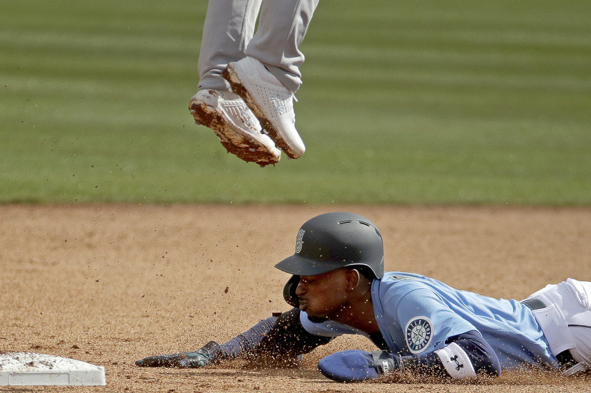 Dee Gordon of Seattle slides under – well under – Oakland second baseman Franklin Barreto to steal a base during Seattle's 8-1 victory.