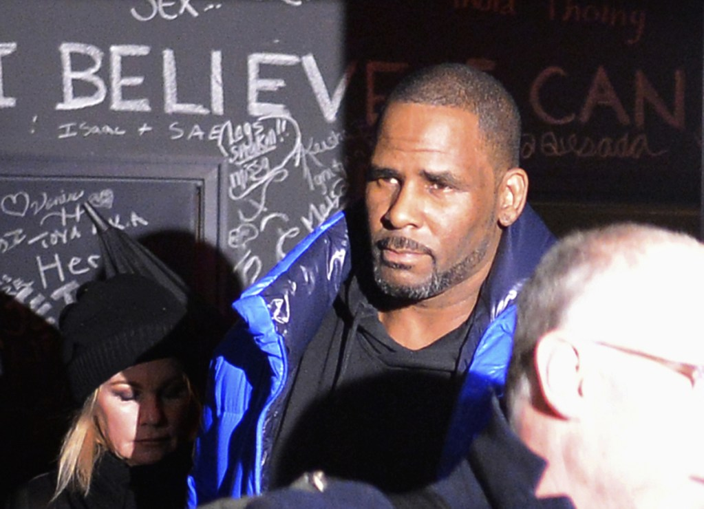 Singer-songwriter R. Kelly leaves his Chicago studio Friday night on his way to surrender to police. He has been trailed for decades by allegations that he violated underage girls and women and held some as virtual slaves.