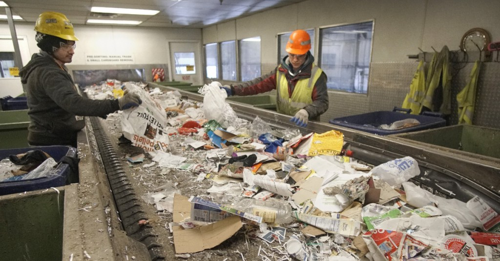 Hector Reinos, left, and Arturo Santos pull out plastics from a conveyor of paper to be recycled at ecomaine in Portland. Plastic is of limited utility on the recycling market.