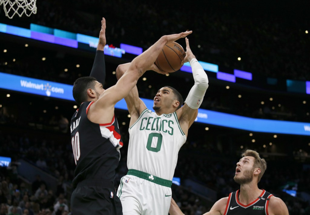 Boston's Jayson Tatum shoots as Portland's Enes Kanter defends during the first half Wednesday night in Boston.