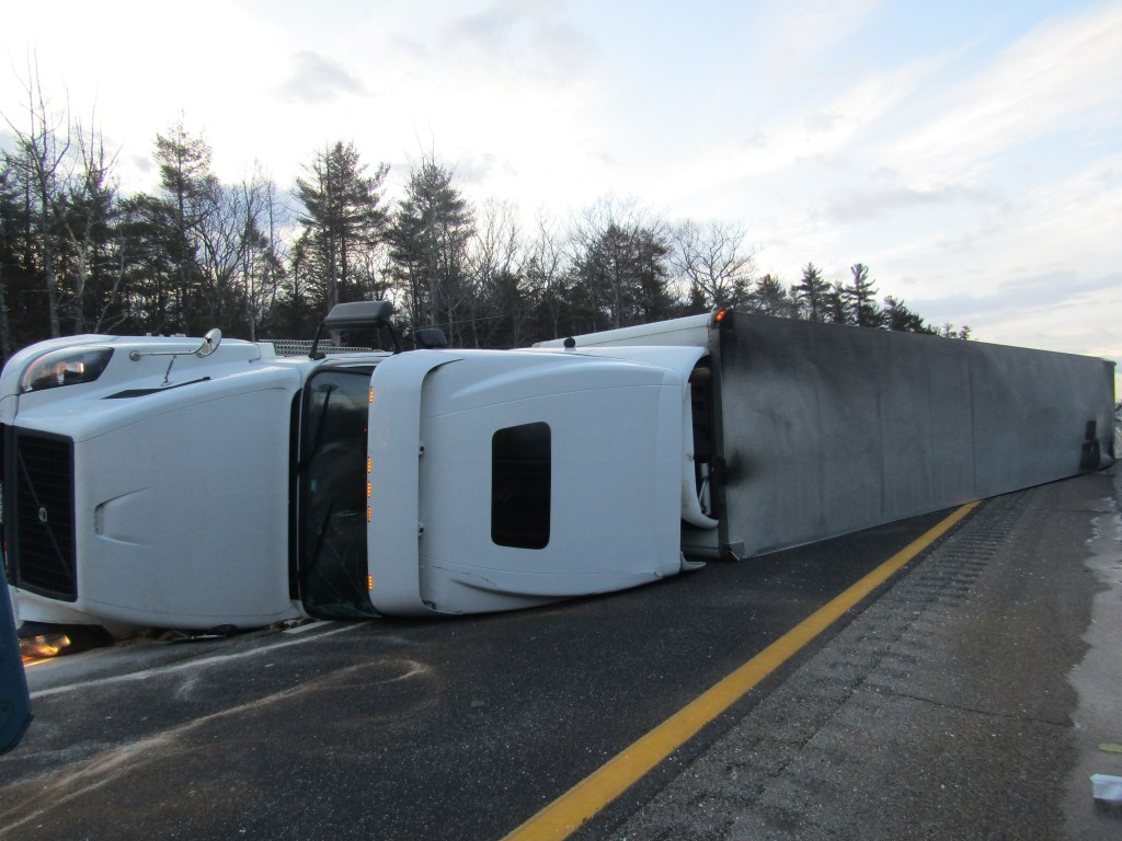 This overturned tractor trailer was slowing traffic on the Maine Turnpike on Monday. Police diverted motorists through the breakdown lane.