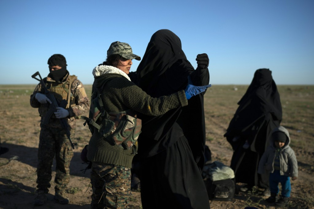 A woman who was evacuated from Islamic State's last redoubt near Baghouz, Syria, is searched by a Syrian Democratic Forces fighter at a screening area on Friday.