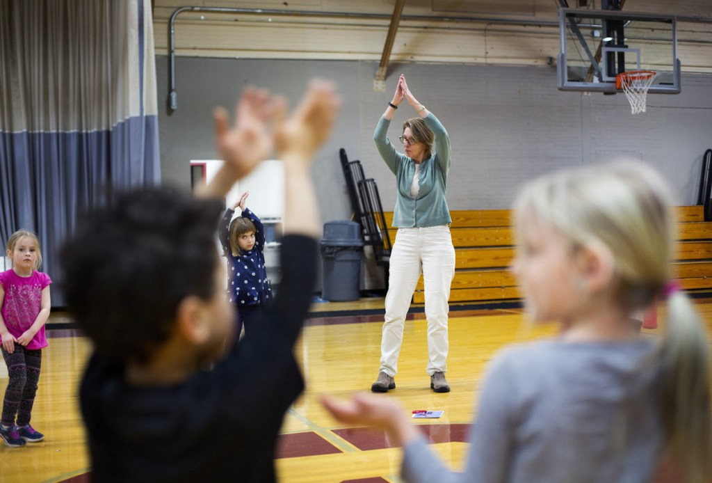Education technician Kathy Robbins leads Saco Community Center pre-kindergartners in a yoga exercise Thursday. Saco and Portland are among school districts planning to apply increased subsidies to expanded pre-K programs.