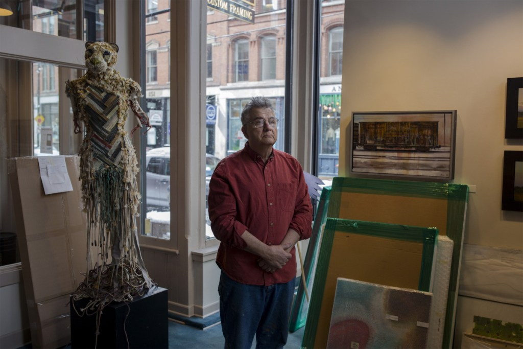 "Portland artist Henry Isaacs watches as his exhibition, ""Travel Notes,"" is set up at Greenhut Galleries in Portland on March 4. The 68-year-old painter and his wife are heading to Nepal next week so that he can paint the world's tallest peak."