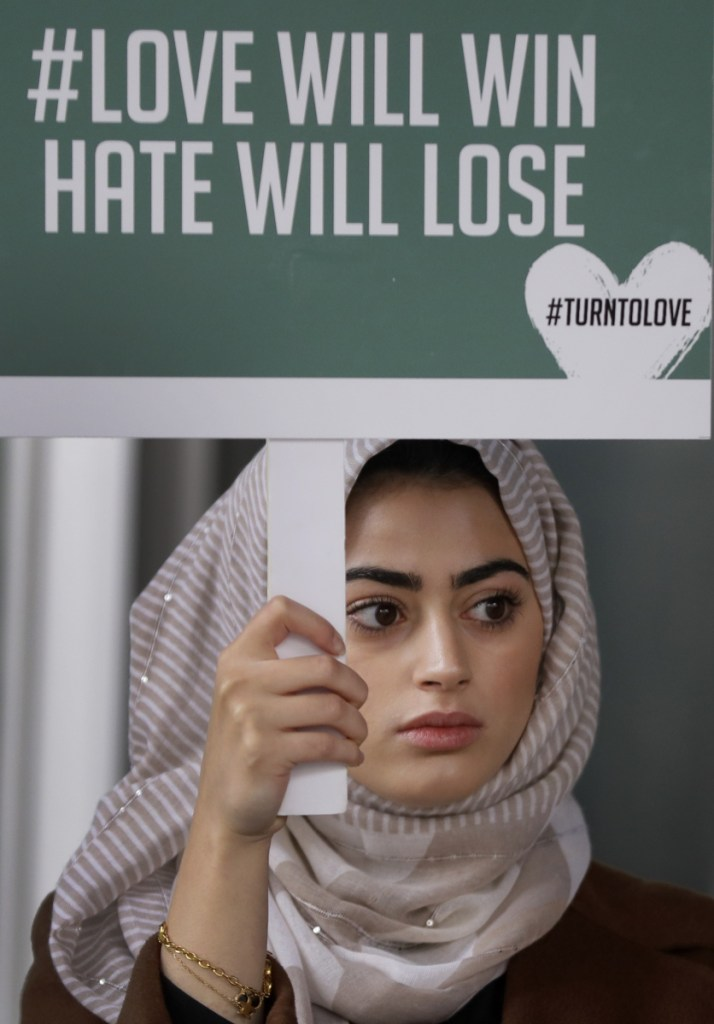 "A demonstrator holds a banner from a multi-faith group, ""Turn to Love,"" during a vigil at New Zealand House in London on Friday following the deadly attacks on two mosques in Christchurch."