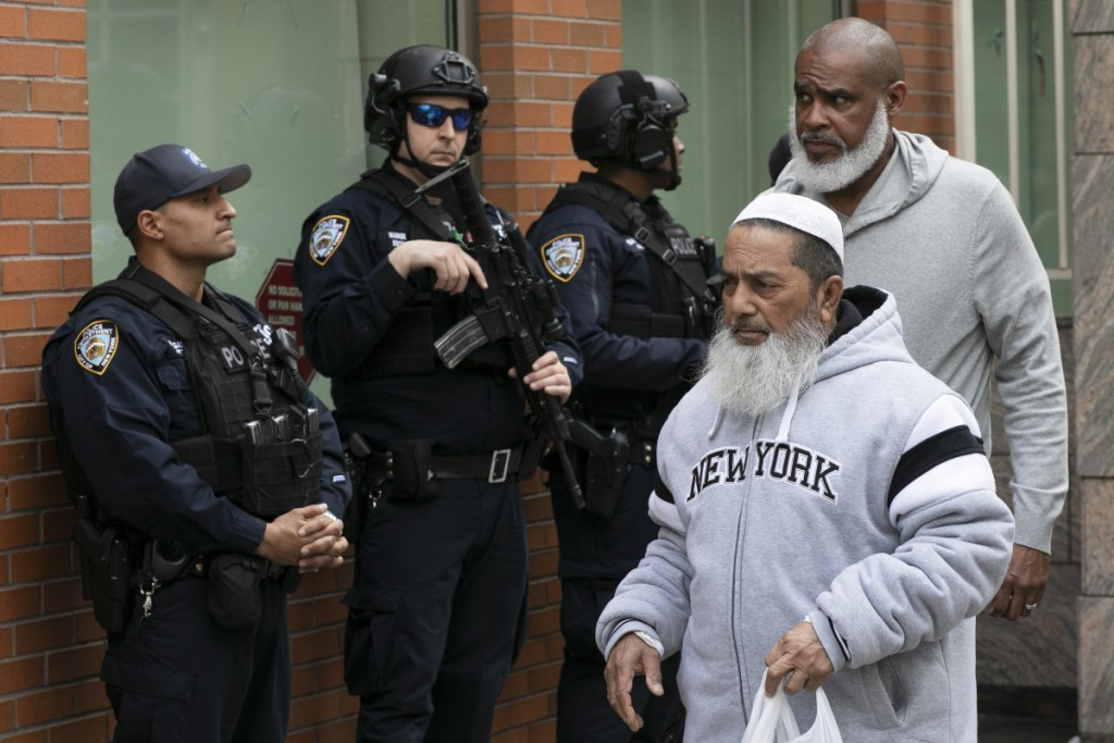 Men leave the Islamic Cultural Center of New York under increased police security Friday following the deadly attacks on mosques in New Zealand.