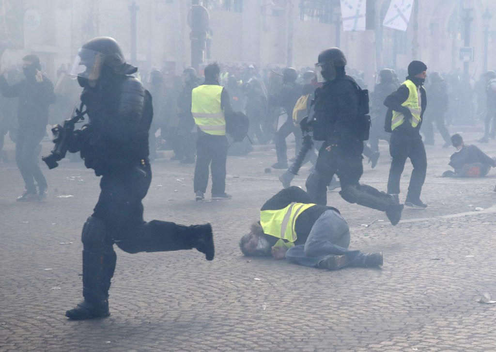 "Riot police charge through a yellow vests demonstration in Paris on Saturday. Protesters say President Emmanuel Macron failed to respond to citizens' concerns about sinking living standards, stagnant wages and high unemployment. ""We're here to show Macron that empty words are not enough,"" said yellow vest demonstrator Frank Leblanc, 62."